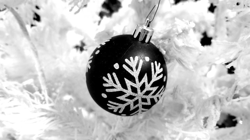 matte black ornament with a sparkly white snowflake on a solid white Christmas tree. Modern Christmas tree