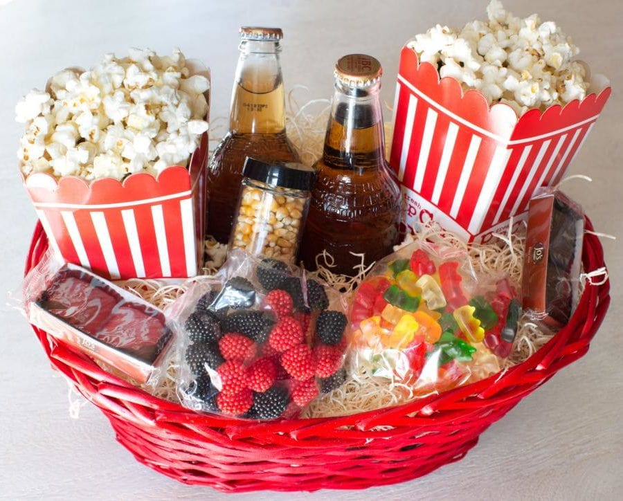 diy movie night basket with soda, popcorn, candy and other goodies for neighbors
