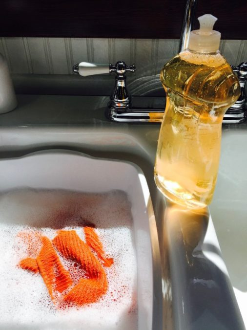 white, sunlit, kitchen sink with shiny chrome vintage fixtures, soapy water with an orange dish rag, and a bottle of orange dish soap diy 3 ingredient ice melt