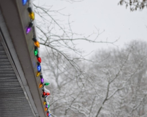 Old fashioned Christmas lights hang from the roof of the house on a snow day
