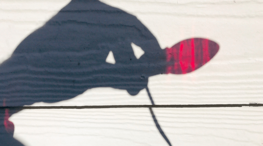 outdoor xmas lights silhouette red bulb and hand against light colored siding