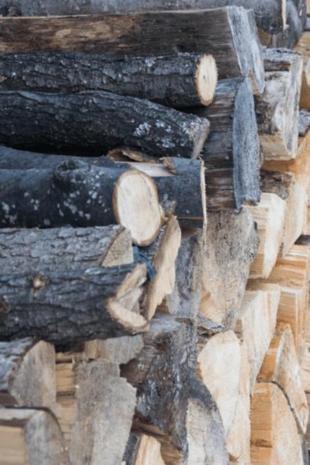 season firewood tall woodpile of seasoned logs outdoors uncovered