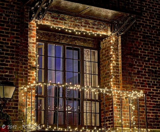 simple apartment blacony christmas decor brick facade white lights