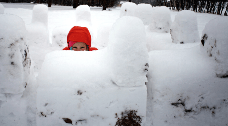 a boy in a heavily fortified snow fort well constructed how to build snow fort protip