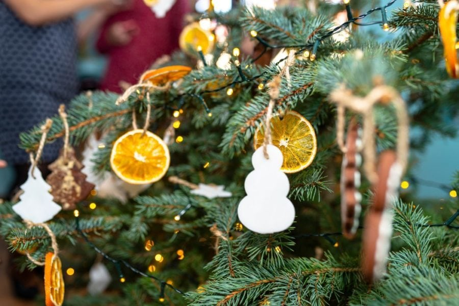 Dried orange slices and a white snowman hanging on a Christmas tree