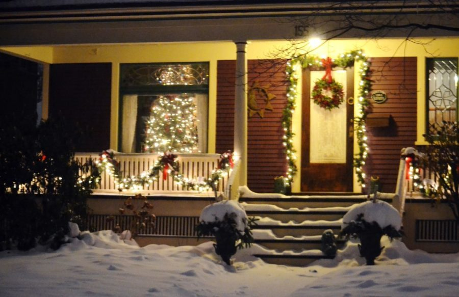 front porch with christmas lights and garland in snow