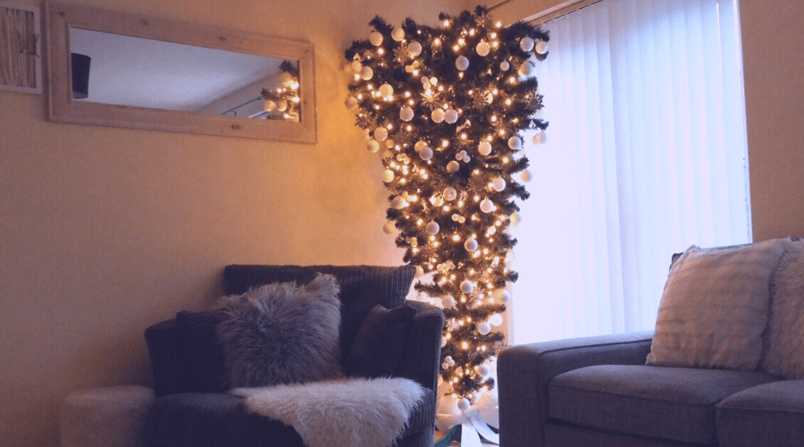 a christmas tree hangs upside down between a sofa and arm chair