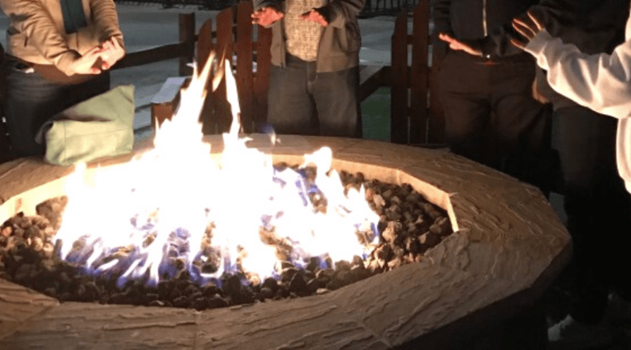 winter fire pit ideas wide featured people standing around concrete fire pit warming hands nighttime winter outdoors
