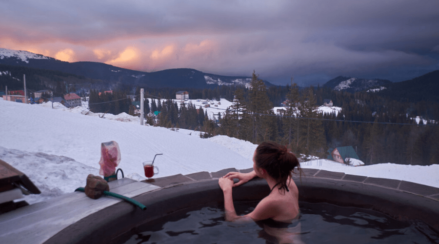 a woman in a hot tub outdoors in winter overlooking mountain view