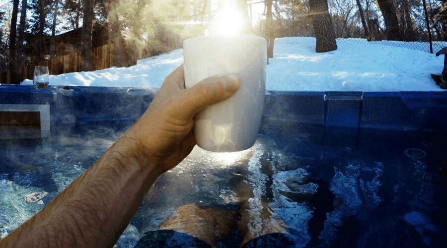 man in hot tub holding drink in winter with snow on the ground