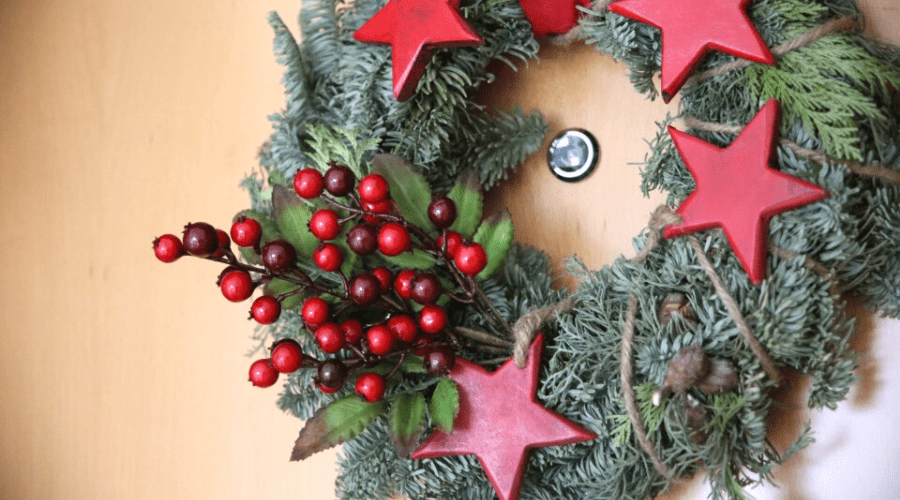 a wreath with winter berries and painted wooden stars hangs on a wooden door
