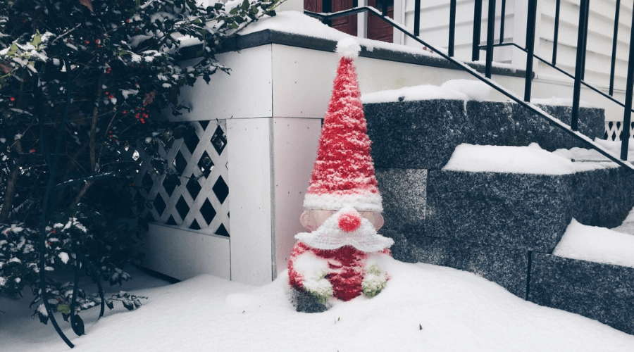 santa garden gnome in snow beside front steps of house