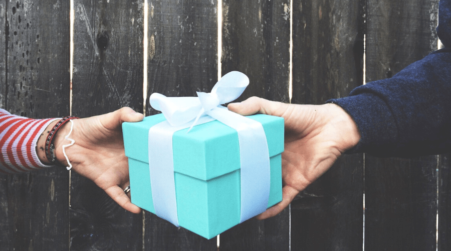 small blue giftwrapped box exchanging hands in front of wooden fence