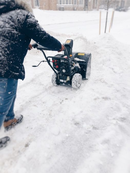 Canadian winter. Man is clearing snow from a driveway with a snowblower
