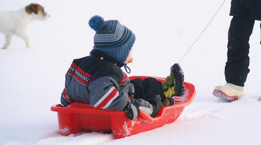 a toddler boy rides in a plastic sled