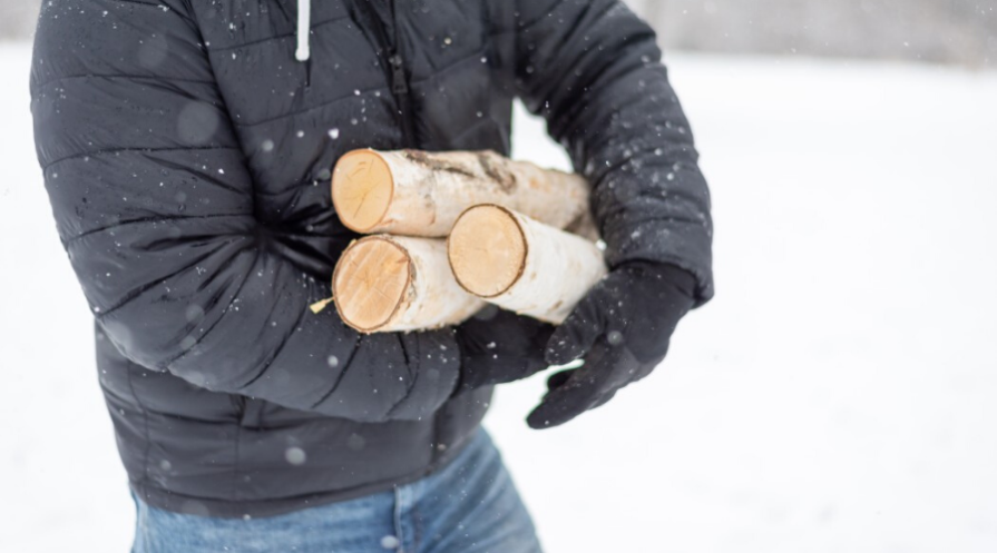 man carrying armload of seasoned birch firewood outdoors in winter