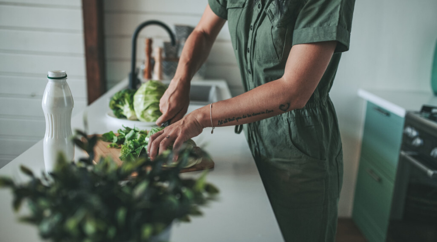 woman cutting escarole and other greens in kitchen