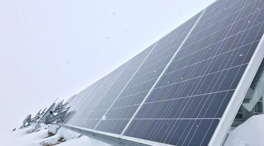 a long line of solar panels with snow falling on them