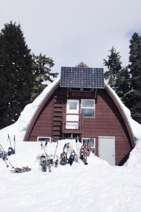 solar panels on the side of a house with snow on the ground