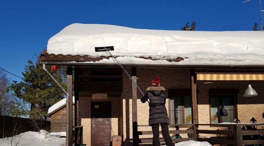 Woman cleans snow with shovel from roof of house, apartment building on clear winter frosty day, St. Petersburg, Russia