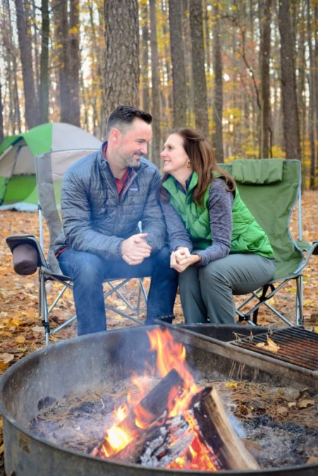 couple sitting beside a campfire in pine forest pine firewood outdoor use