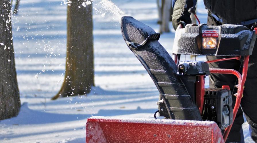 troy bilt snowblower in use on gravel drive