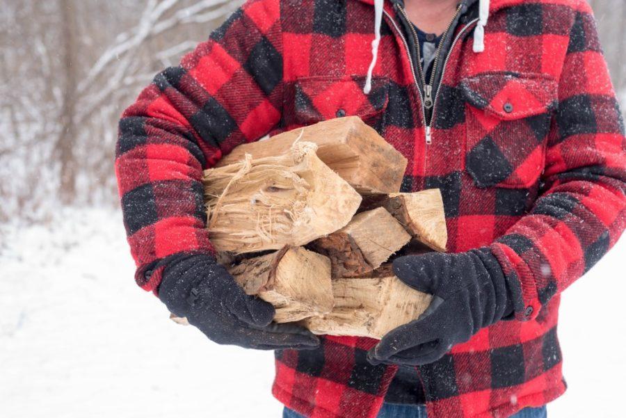 twenty20_man carrying split firewood outdoors in winter