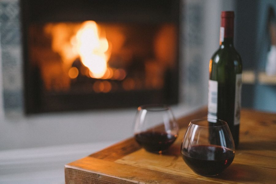 interior shot of home with wine in foreground and burning fire in background