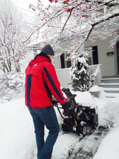 man using snowblower on front sidewalk walkway drive winter