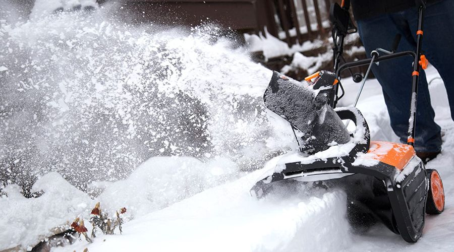 Corded electric snow blower eating through a snow bank.
