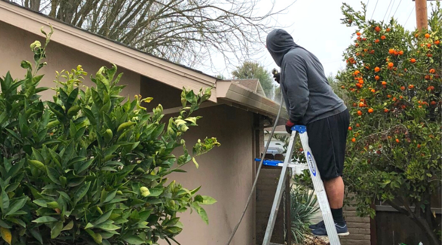 A man in a hoodie sprays out gutters before using cleaning solution