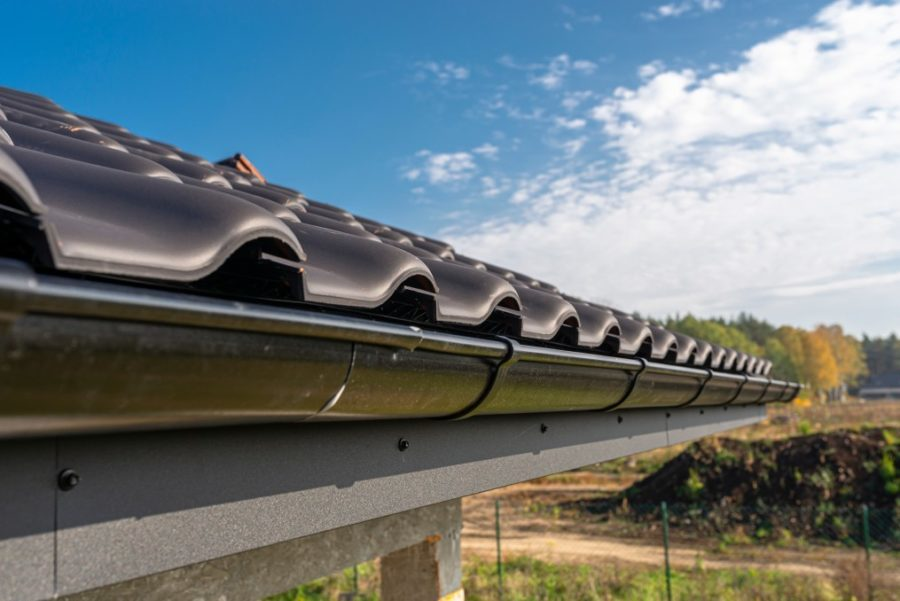A metal, black gutter on a roof covered with ceramic tiles. Close up shot. roof gutter