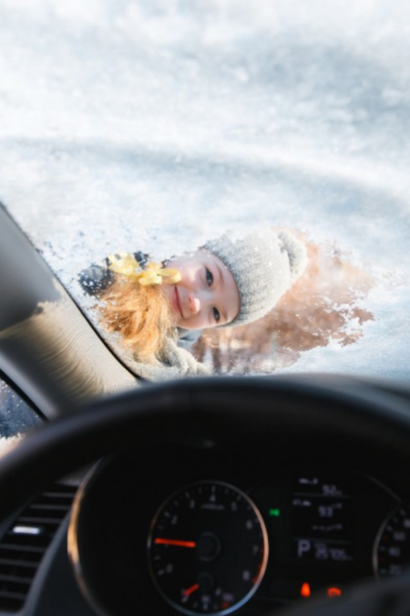 child smiling through a snowy windshield ice scraper clear windows vehicle