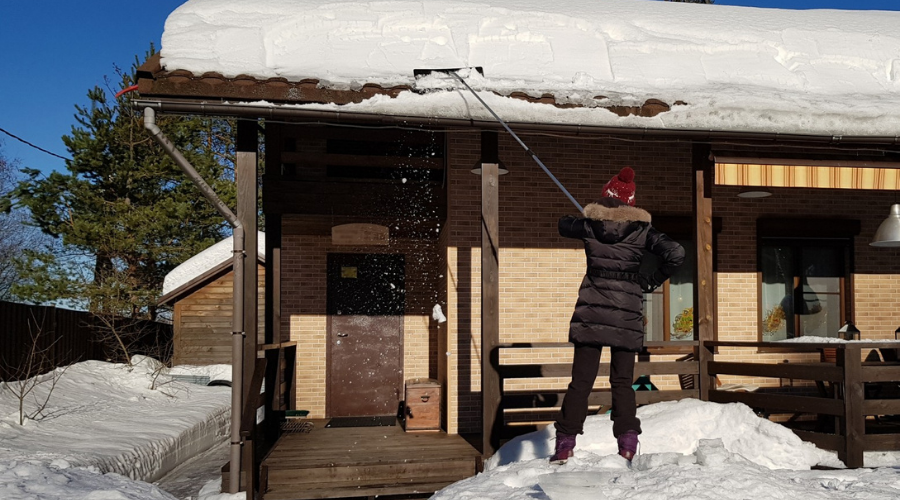 a woman uses a roof rake to clear snowfall from house in winter
