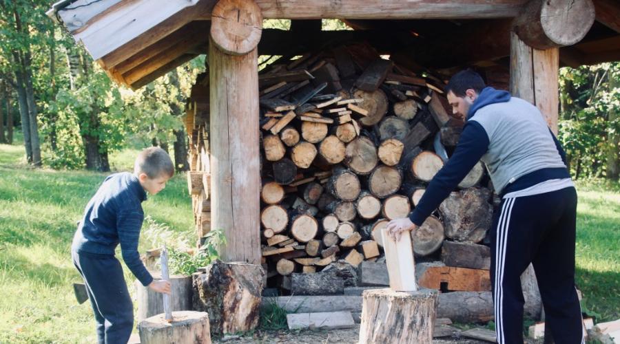 man and boy split firewood near diy firewood storage rack outside