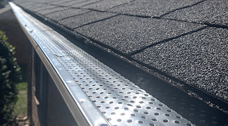a gutter with gutter guards installed on a shingled roof closeup