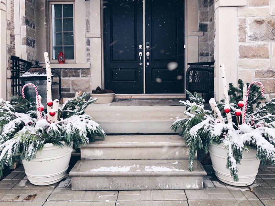 Front porch of a house decorated for Christmas and it's snowing