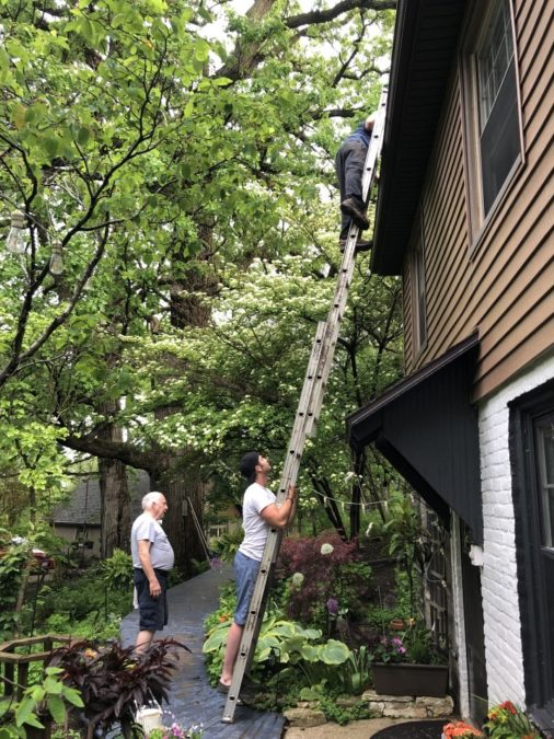 men on ladder cleaning gutters at home