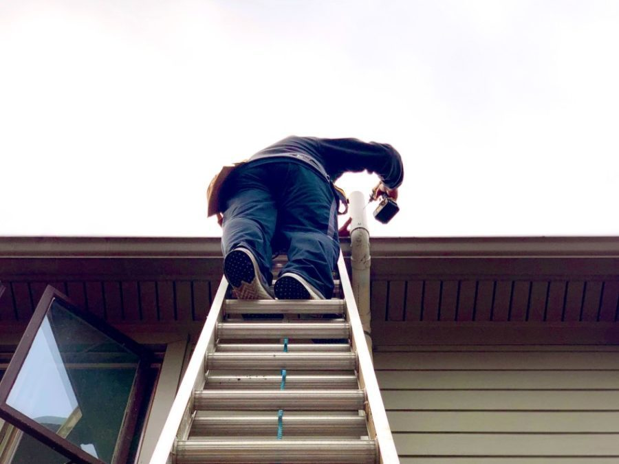 man on ladder to roof