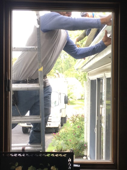 Man on ladder installing new gutters on home, ladder, outdoor, home improvement, installation,