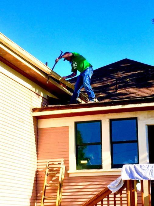 a man installs new gutter guards himself on a home