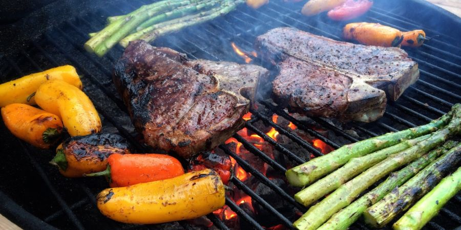 Charcoal grill with sizzling steaks and veggies.