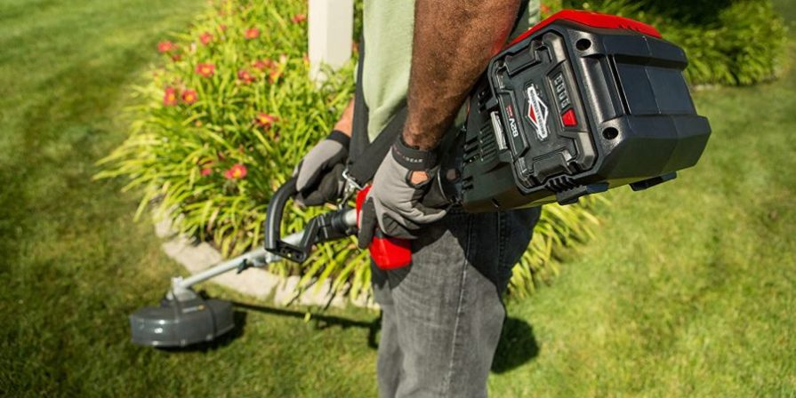 Man holding a battery-powered string trimmer while cutting lawn around a flower bed.