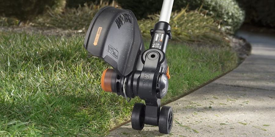 Cordless string trimmer doubling as an edger, cutting the edge of a lawn.