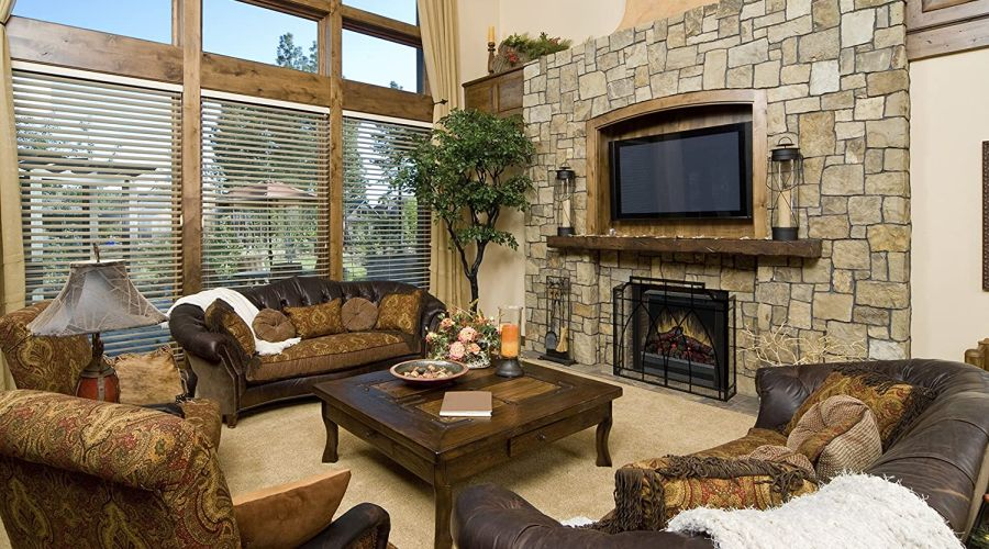 Cozy country home loving room with a set of leather couches and armchairs arranged around a burning electric fireplace.