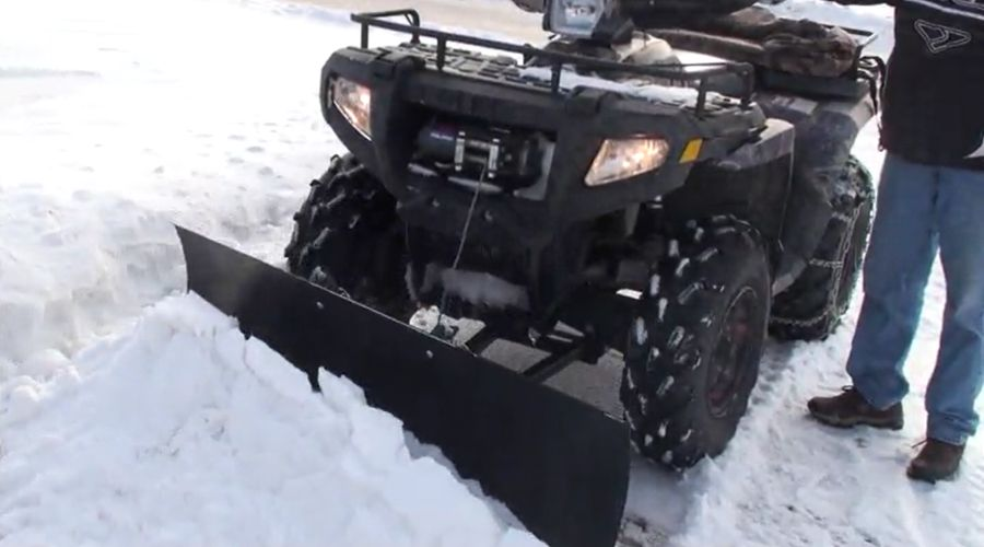UniPlow Extreme Max snowplow attached to an ATV, operating in the snow.