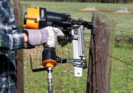 Man stapling metal wire to a post with a fencing stapler.