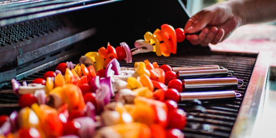 Veggie skewers cooking on a gas grill.