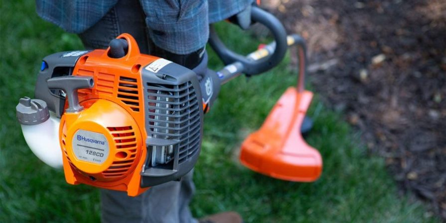 Man using a Husqvarna edge trimmer to trim the lawn.