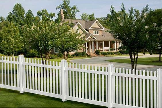 a white picket fence with trees and a house in the background